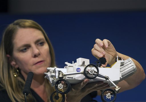 Jennifer Trosper, Mars Science Laboratory, MSL mission manager, JPL, adjusts the high-gain antenna on a rover model during a news briefing on the last data and imagery from Sol 1 at NASA's Jet Propulsion Laboratory in Pasadena, Calif., on Monday.