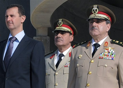 Syrian President Bashar Assad, left, stands next to then-Defense Minister Gen. Dawoud Rajha, right, during an Oct. 6, 2011, ceremony in Damascus. Rajha was killed in a suicide attack on July 18, 2012. The man at right is unidentified.