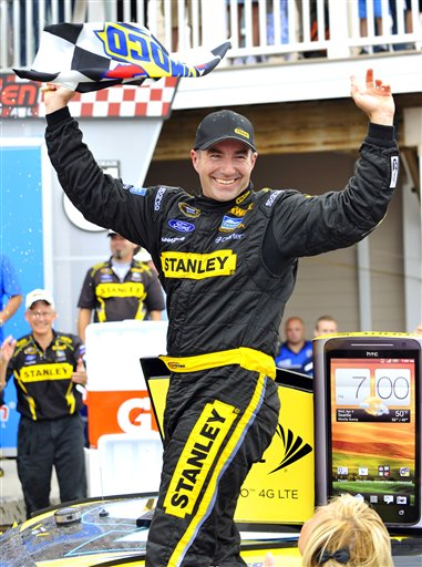 Marcos Ambrose stands on his car in victory lane as he celebrates his win at the NASCAR Sprint Cup Series at Watkins Glen International on Sunday in Watkins Glen, N.Y. 2012;Finger Lakes 355;NASCAR;Race;Watkins Glen International;August;Sprint Cup Series;Watkins Glen;New York;Autostock