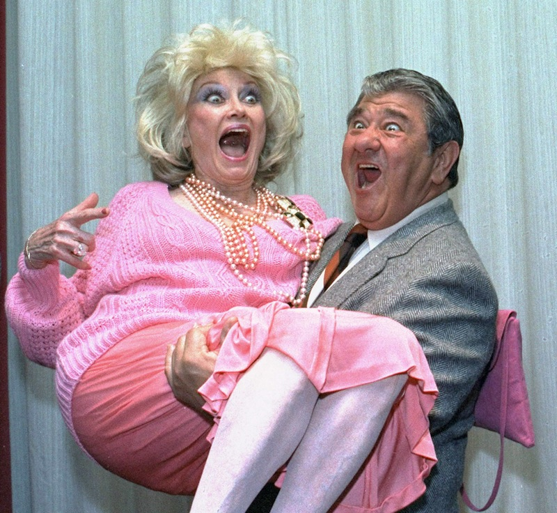 In this Oct. 9, 1985, file photo, Comedian Phyllis Diller gets a lift from emcee Buddy Hackett prior to the celebrity stag luncheon roast at the New York Friars Club in New York City. Diller, the housewife turned humorist who aimed some of her sharpest barbs at herself, died Monday, Aug. 20, 2012, at age 95 in Los Angeles. (AP Photo/Marty Lederhandler, File)
