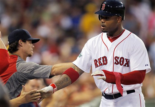 Boston Red Sox's Carl Crawford is welcomed to the dugout after scoring on a double hit by Adrian Gonzalez in the third inning Monday at Fenway Park in Boston.