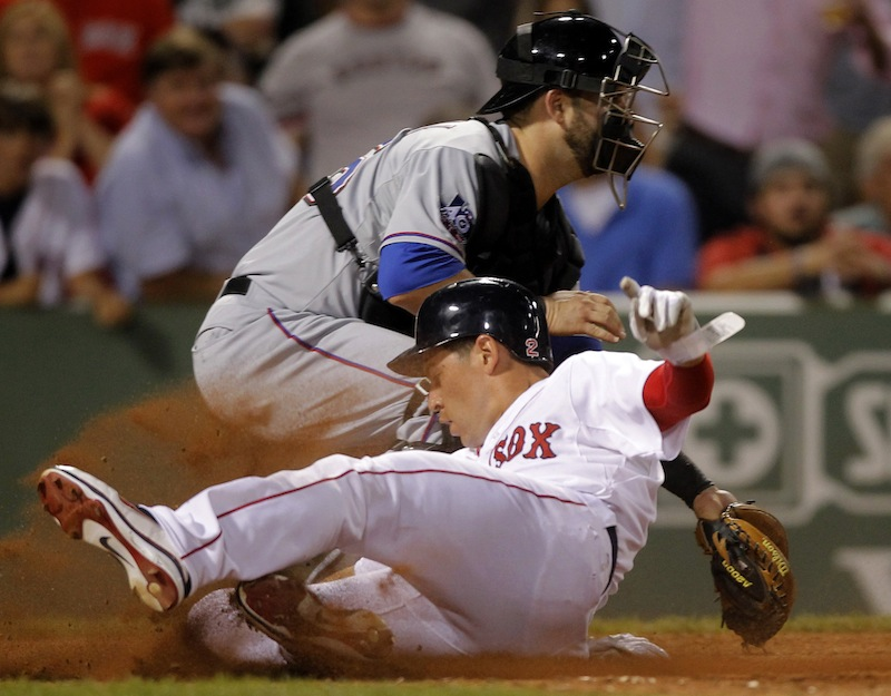 Boston Red Sox's Jacoby Ellsbury, front, scores on a double hit by Red Sox's Carl Crawford as Texas Rangers catcher Mike Napoli, behind, waits for the ball in the eighth inning of a baseball game at Fenway Park, in Boston, Monday, Aug. 6, 2012. (AP Photo/Steven Senne)
