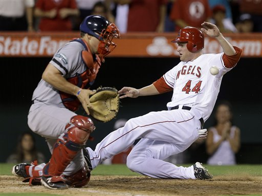 Los Angeles Angels' Mark Trumbo, left, scores on a double by Howard Kendrick past Boston Red Sox catcher Ryan Lavarnway during sixth inning of an baseball in Anaheim, Calif., Tuesday, Aug. 28, 2012. (AP Photo/Chris Carlson)