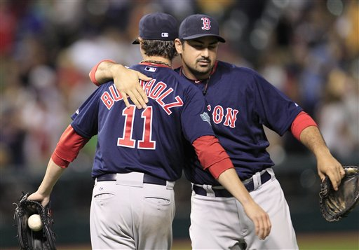 Boston Red Sox's Adrian Gonzalez, right, hugs pitcher Clay Buchholz after the Red Sox defeated the Cleveland Indians 3-2 in a baseball game, Friday, Aug. 10, 2012, in Cleveland. (AP Photo/Tony Dejak)