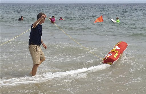 Misquamicut, R.I., Fire Chief Louis Misto, left, holds a line attached to the EMILY remote-control lifesaving device as it propels itself in the water and away from the shore at Old Town Beach, in Westerly, R.I.