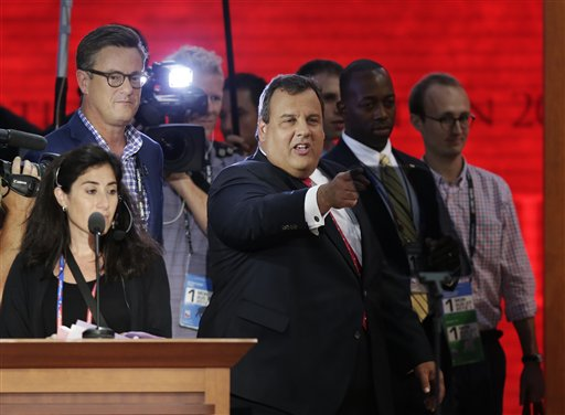 New Jersey Gov. Chris Christie, right, stands on the main stage before the start of the Republican National Convention in Tampa, Fla., on Monday.