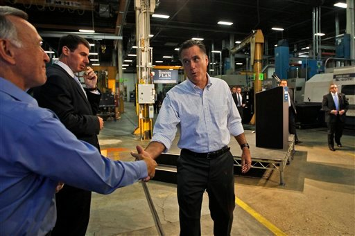 Republican presidential candidate Mitt Romney greets with Warren Young, chief executive officer at Acme Industries, as he campaigns in Elk Grove Village, Ill., today.