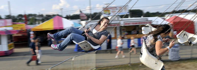 Staff photo by Michael G. Seamans Krista Rogers, 19 left, and Megan Miville, 19, both of Fairfield, spin around on the Trapeze Swings at the Skowhegan State Fair Wednesday.