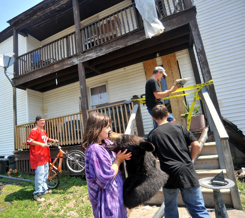Brooke Robinson, front center, kisses the head of a bear that was salvaged from Jeff White's, far back, apartment as they sort through salvageable belongings from their apartment on Drummond Avenue in Waterville on Thursday.