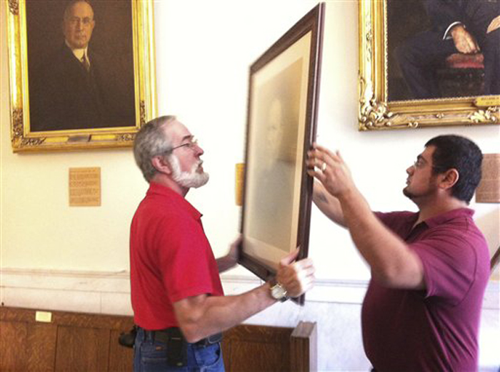In this still image from video provided by WMUR-TV, workers on Wednesday remove a portrait purported to be former Gov. Henry Keyes.