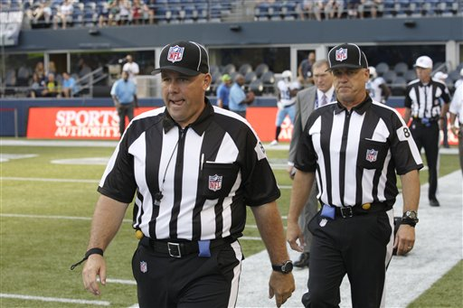 Replacement officials take the field at the start of an NFL football preseason game between the Seattle Seahawks and the Tennessee Titans last Saturday in Seattle.