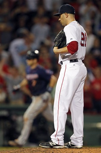 Boston Red Sox's Alfredo Aceves looks down after giving up a three-run home run to Minnesota Twins' Joe Mauer, left, in the ninth inning of a baseball game in Boston, Saturday, Aug. 4, 2012. The Twins won 6-4. (AP Photo/Michael Dwyer)