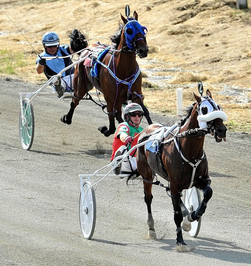 ON THE WAY TO VICTORY: Gary Mosher, foreground, drives Wholly Louy to the win during the Walter H. Hight Invitational Saturday at the Skowhegan Fairgrounds. Mr Nice Guy, driven by Kevin Switzer, background, finished second .