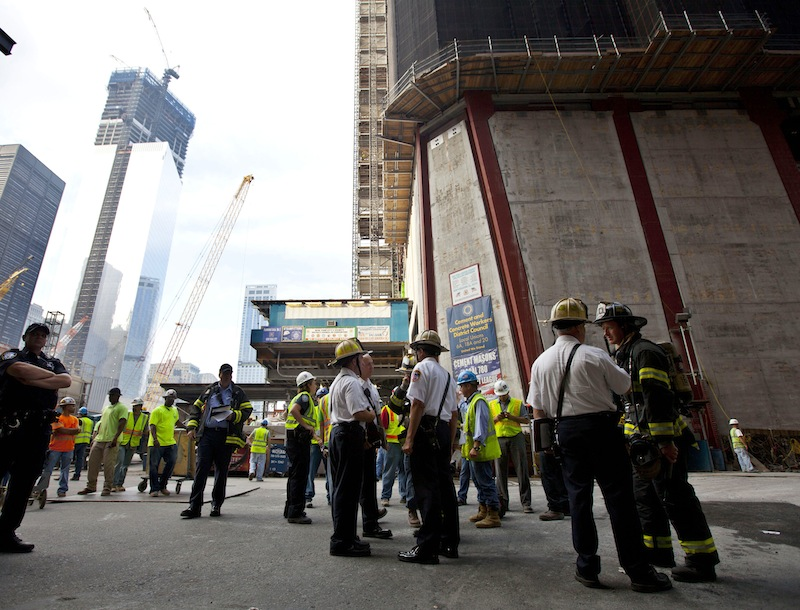 New York City firefighters gather at the base of One World Trade Center, right, where they were summoned by a report of a fire that turned out to be someone welding, Wednesday, Aug. 8, 2012, in New York. The fire department says it received a report of a fire on the 88th floor of One World Trade Center at ground zero shortly before 8 a.m. but a spokesman for the Port Authority of New York and New Jersey, which owns the site, said the report, by a member of the the public, was believed to be a false alarm. (AP Photo/Jin Lee)