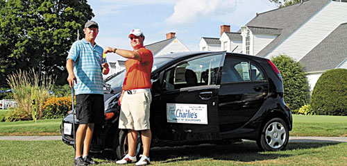 HERE'S YOUR KEYS: Mike DuBois of Benton, left, poses with Steve Shuman of Charlie's Motor Mall after DuBois won an electric car in a tournament last week at the Augusta Country Club in Manchester.
