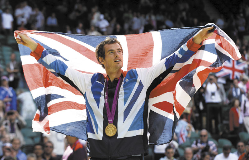 HOMETOWN HERO: Andy Murray waves the British flag during the medal ceremony for men's singles tennis Sunday at the All England Lawn Tennis Club at Wimbledon in London. 2012 London Olympic Games Summe