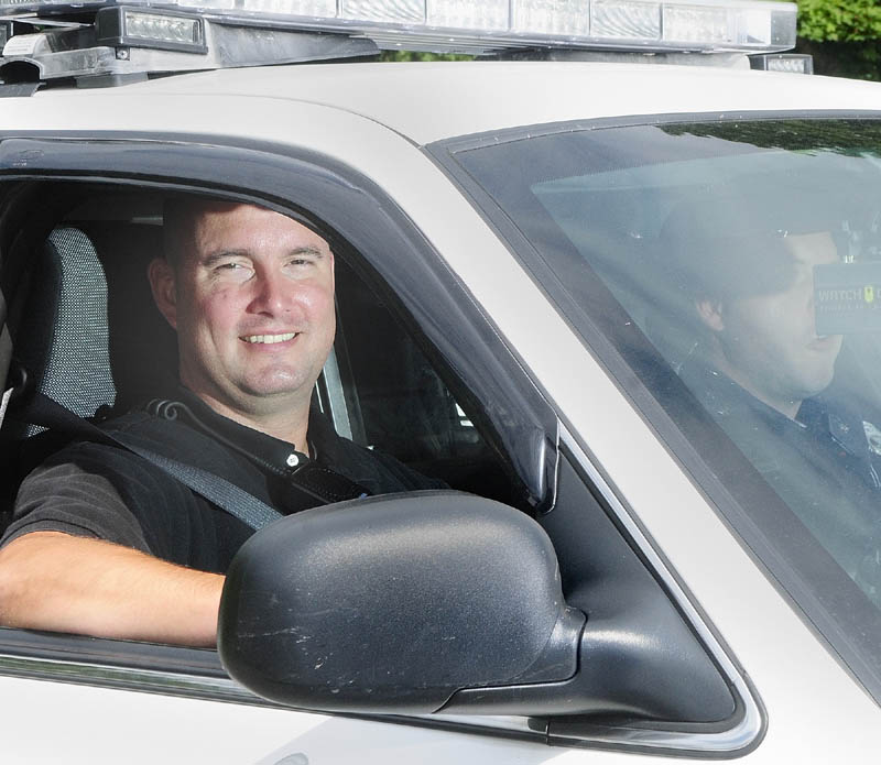Greg Smith, the department's intensive case manager, sits in the passenger side of an Augusta police cruiser driven by Officer Nathan Walker on Wednesday afternoon.