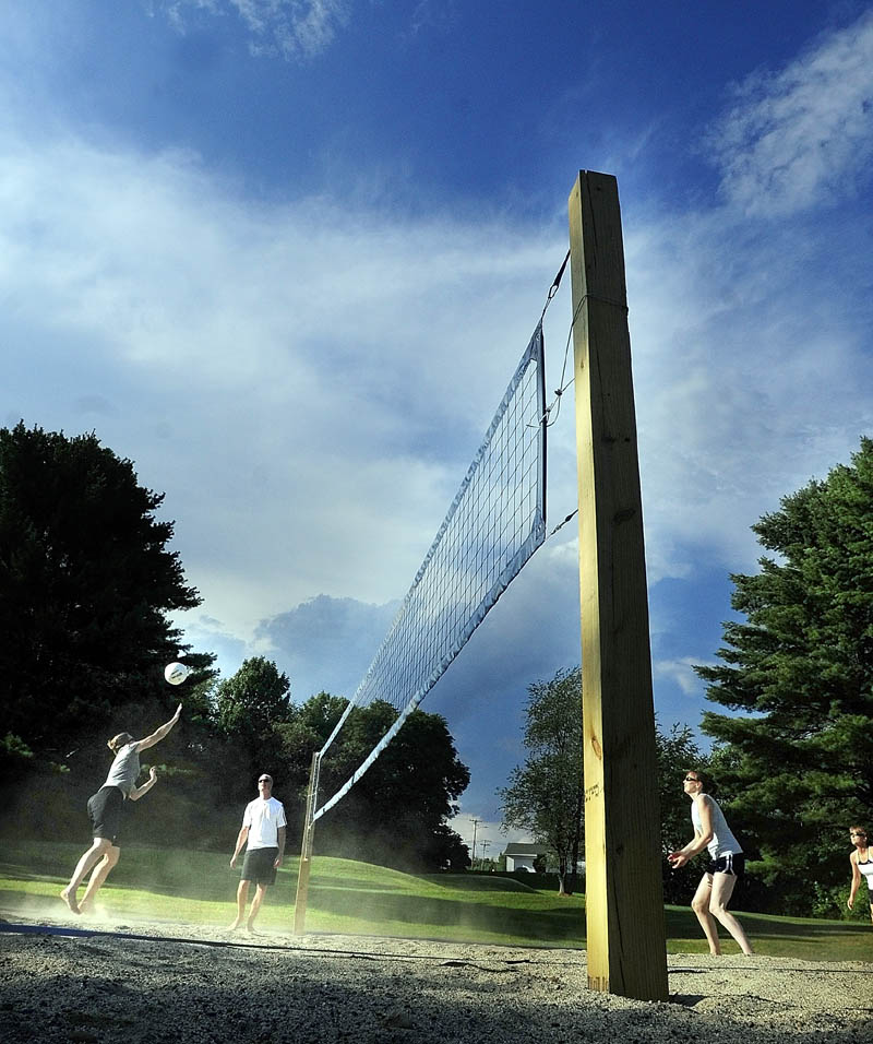 Players hit the ball during a practice session on Friday evening at the new beach volleyball court at Youth Memorial Park in Augusta. The courts are behind the Buker Center near the corner of Capital Street and Alden Avenue.