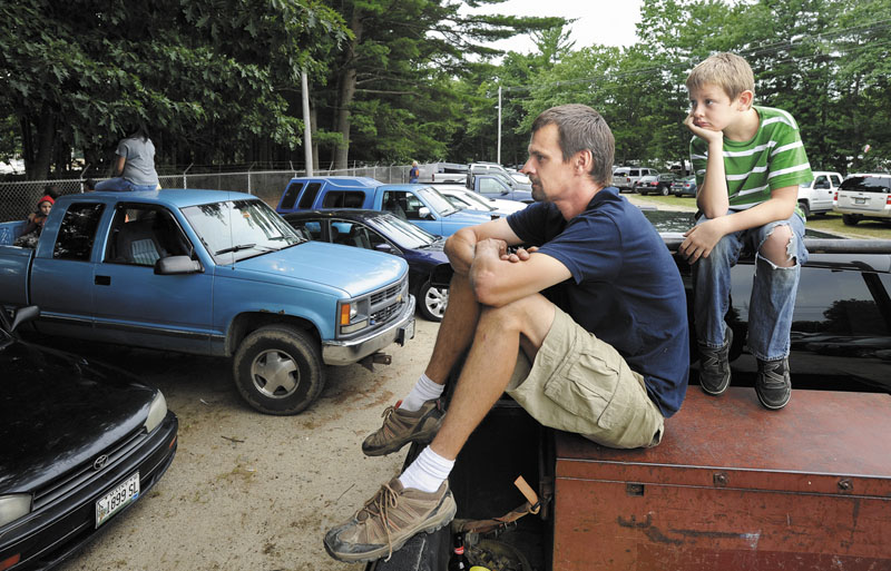 Perched atop a pickup truck to get an elevated view, Matt Hodgdon of Scarborough and his son, Josh, 10, watch stock car racing over the fence of the Beach Ridge Motor Speedway in Scarborough, Saturday, July 28.
