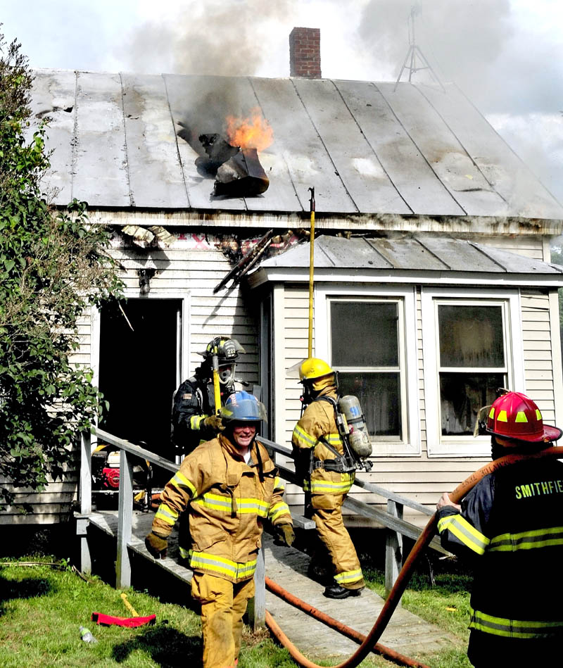 Flames shoot up through the roof of a home on the Smithfield Road in Belgrade that was destroyed by fire on Monday. The stubborn fire began in the rear of the building and eventually moved to the front despite the efforts of firefighters from six departments.