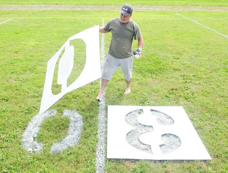 JUST RIGHT: Bruce Brooks lifts up a stencil after spray painting a zero last week on Maxwell Field where the Winthrop Ramblers play football games. The Ramblers open their season tonight on the road against Sacopee Valley in Hiram.