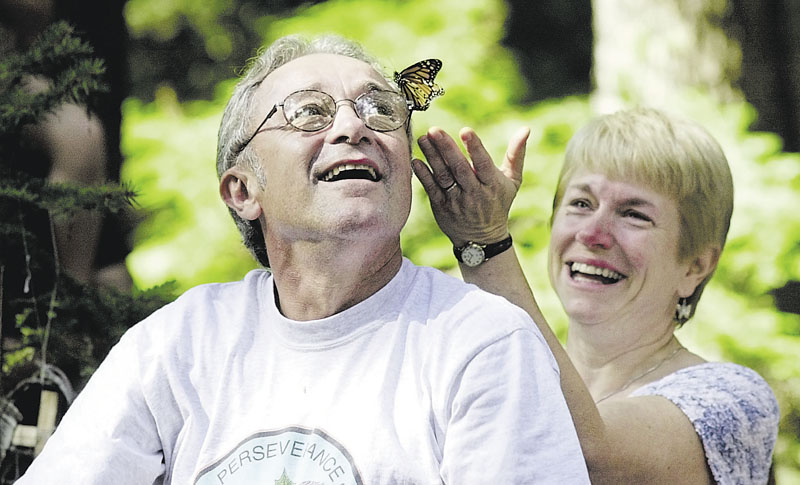 CAMP RAY OF HOPE: Mimi Roughgarden reaches out to a Monarch butterfly that landed on the temple of her husband, Rich, moments after he released it in memory of their late daughter, Cara. They were attending Camp Ray of Hope.