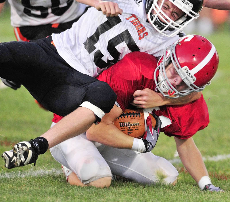 TOUGH TACKLE: Gardiner's Justin Lovely tackles Cony's Brandon St. Michel during last year's 134th Cony-Gardiner football game at Alumni Field in Augusta. The teams kick off their seasons this Friday night.