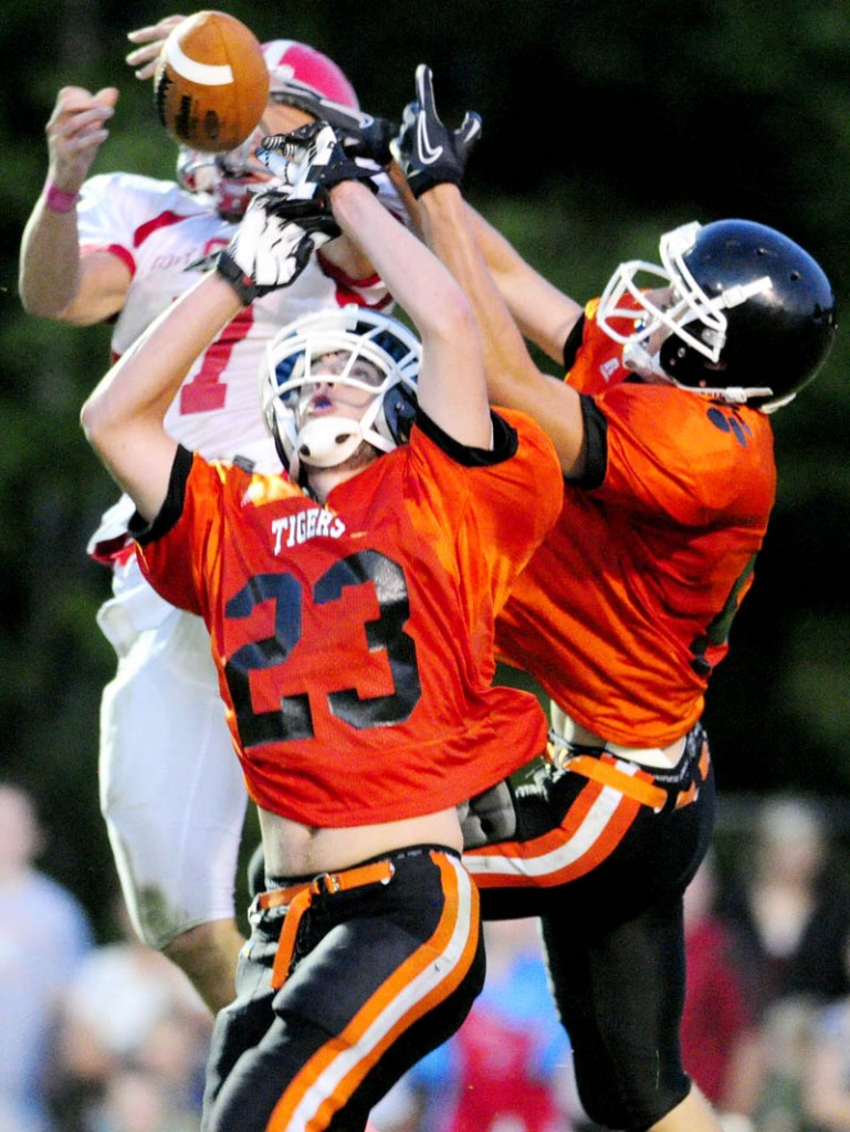 Cony wide receiver Chandler Shostak, top left, can't hang onto the pass as he is double teamed by Gardiner defenders Tyler Jamison, center, (23) and Josh Moore during the Drive Out Cancer Challenge game at Hoch Field on Friday in Gardiner.