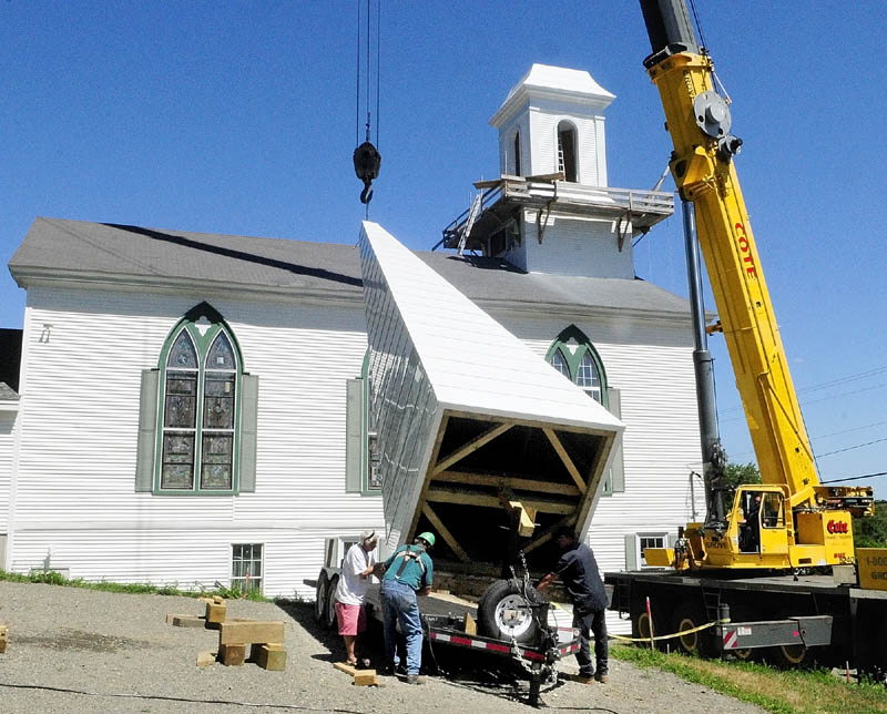Cox Memorial Methodist Church hired steeplewright Robert Hanscom, second from left, to remove the old steeple, and build and install a new one. After being gone since last fall, a new steeple with a weather vane was put back up Tuesday morning at the corner of Middle and Central streets in Hallowell.