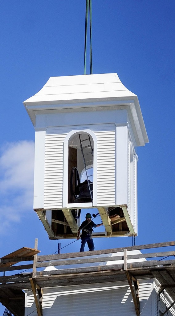 A crane lowers the bell tower that steeplewright Robert Hanscom built on to the steeple on Tuesday morning at the corner of Middle and Central streets in Hallowell.