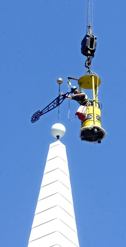 Staff photo by Joe Phelan Working from a bucket hanging from a crane, steeplewright Robert Hanscom put a new weathervane on top of the new steeple he built on Tuesday morning at the corner of Middle and Central Streets in Hallowell.