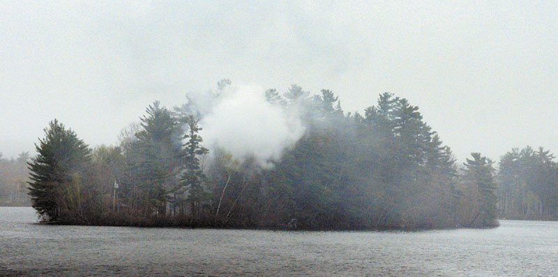 Smoke rises from a structure fire on an island in Togus Pond on Friday evening.