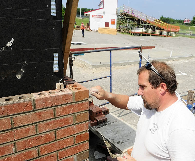Fred Scannell, of One Over Two Masonry, mortars the joints in the brick veneer on new ticket booths at the entrance to Alumni Field at Cony High School in Augusta on Friday afternoon.