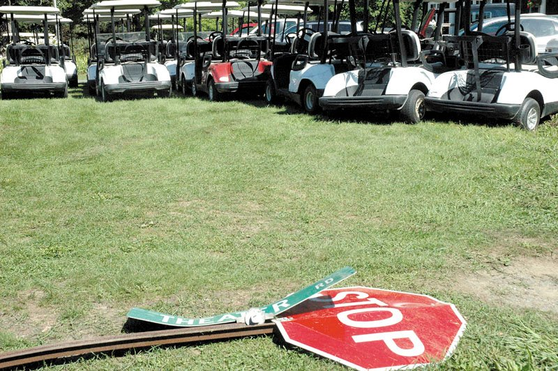 The sign for Theater Road and a stop sign lay flattened in front of a row of damaged golf carts at Lakewood Golf Course in Madison.