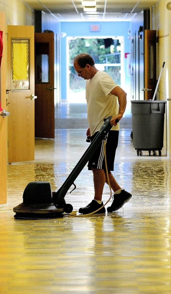PREPARING: Matt McGowan runs a floor stripper down a hallway in James H. Bean School on Wednesday morning in Sidney. He and other staffers were getting ready for the 2012-13 school year that will begin Aug. 29.
