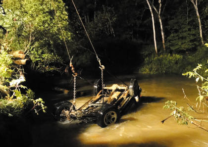 A Jeep submerged in Bond Brook in Augusta on Thursday night is towed back to shore. Police on Friday were still searching for the driver, who fled from the scene.