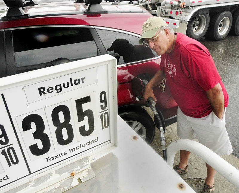 Joe Wutka fills up his gas tank on Friday afternoon at Zoom In on State Street in Augusta.
