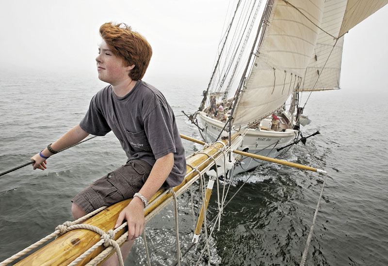Sawyer King, 12, the son of the captain, rides on the bowsprit of the 90-foot passenger schooner Mary Day, while sailing on a foggy afternoon Aug. 2 in East Penobscot Bay off Little Deer Isle. The Mary Day, which is celebrating its 50th season, is the first schooner in the Maine windjammer fleet to be built specifically to accommodate passengers. Its sleeping cabins are heated and have nine feet of headroom.