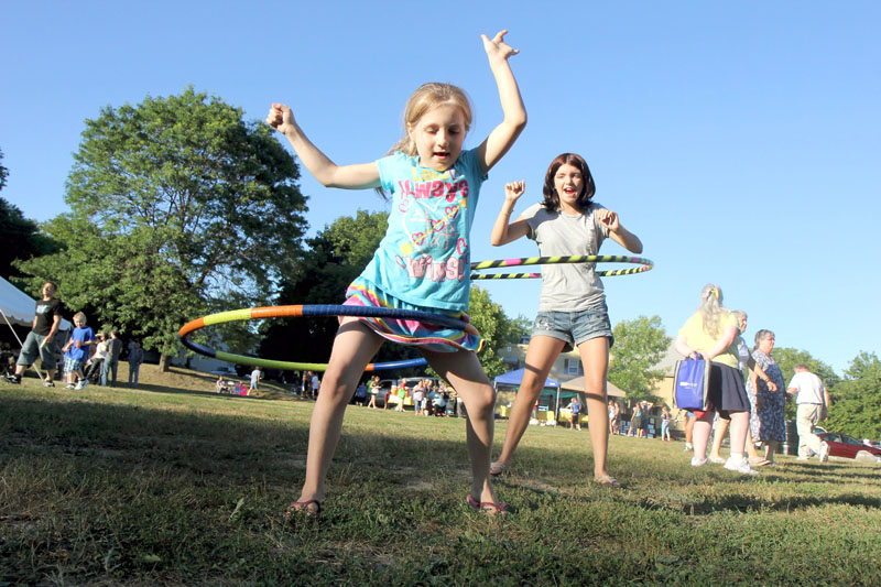 Rayvin Creamer, 7, plays with a hula hoop as her aunt Cassidy Hartin, 12, looks on at National Night Out in Waterville on Tuesday. The annual event was hosted by the Waterville Police Department, the South End Neighborhood Association and the South End Teen Center.