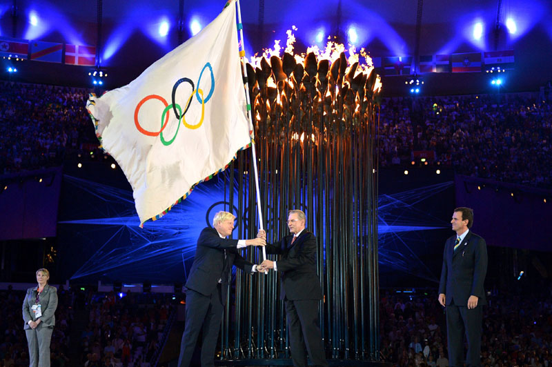 SYMBOLIC GESTURE: The Olympics flag is handed from London Mayor Boris Johnson, second from left, to International Olympic Committee President Jacques Rogge, as Rio de Janeiro Mayor Eduardo Paes watches during Sunday's closing ceremony of the 2012 Olympics in London. Diving