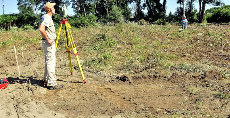 Surveyors Bob Knowlton, left, and Frank Siviski of Broken Stone Survey company, work in the cleared area off Colby Circle in Waterville on Monday where the new police station will be built.