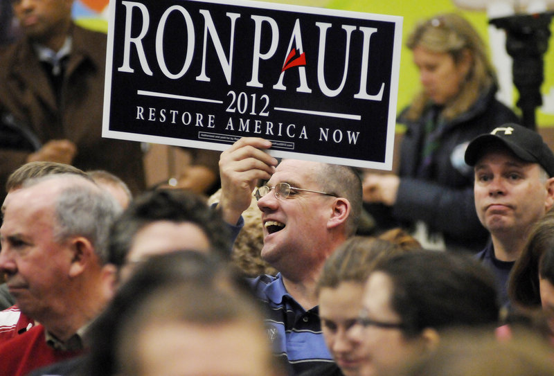 Glenn Strout of Portland holds a sign in support of Texas Rep. Ron Paul during the Portland Republican City Committee Caucus in February. The fate of Maine's delegation to the Republican National Convention remained murky on Tuesday as delegates loyal to Ron Paul continued to negotiate with national party leaders intent on presenting a unified front for Mitt Romney at next week's mega-event.