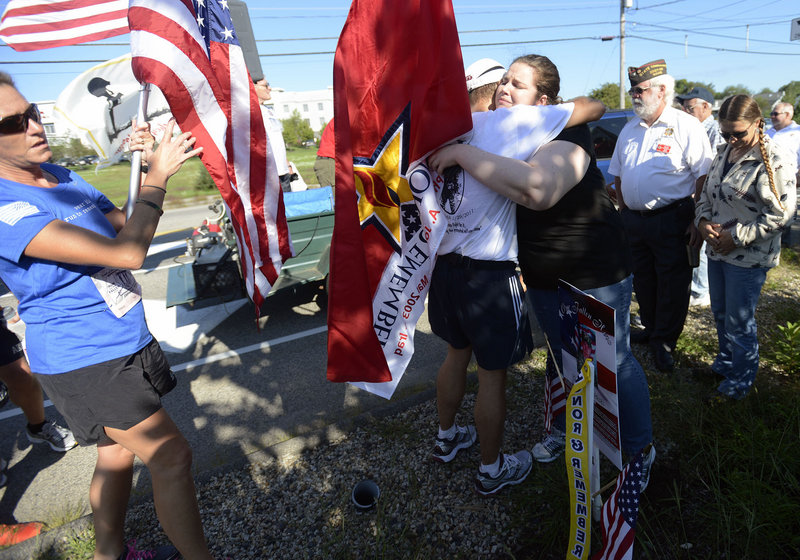 Runners stop to give Meghan Slack of Waterville a hug during the Run for the Fallen along the route in Wells on Sunday. Slack lost her brother Spc. Wade Slack of Waterville, who died while serving in the Army in Afghanistan in 2010.