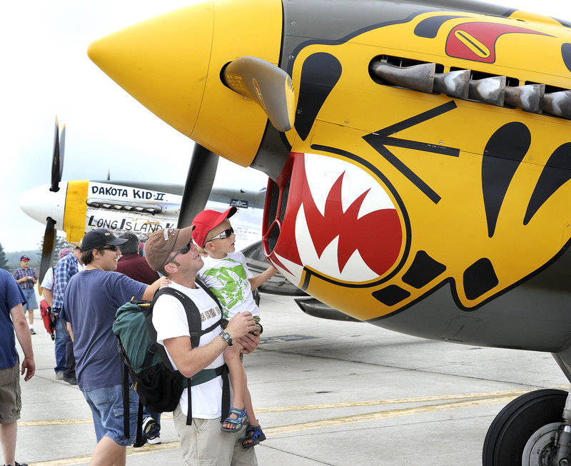 Ty Giberson of Dixfield and his 4-year-old son, Mitchell, check out a World War II P-40 fighter owned by the Texas Flying Legends Air Museum at the air show on Saturday.