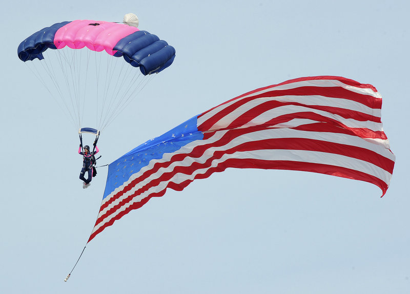 A member of the Misty Blues all-woman skydiving team trails the American flag during the opening ceremony at The Great State of Maine Air Show in Brunswick on Saturday.