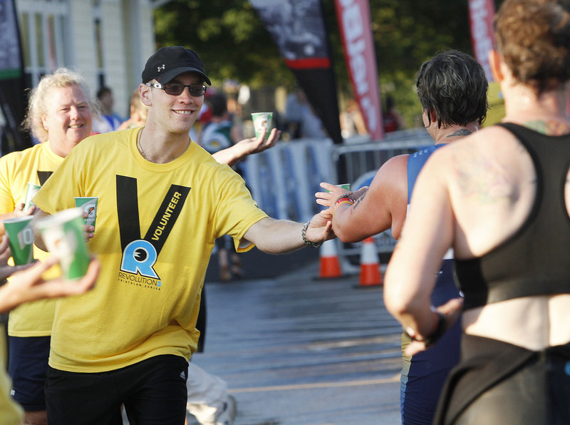 Stephen Gagnon of Portland and Jeanette Strickland of Westbrook, part of a group of volunteers from the Maine Masters Swim Club, hand out water to competitors during the Revolution3 triathalon in Old Orchard Beach on Sunday.