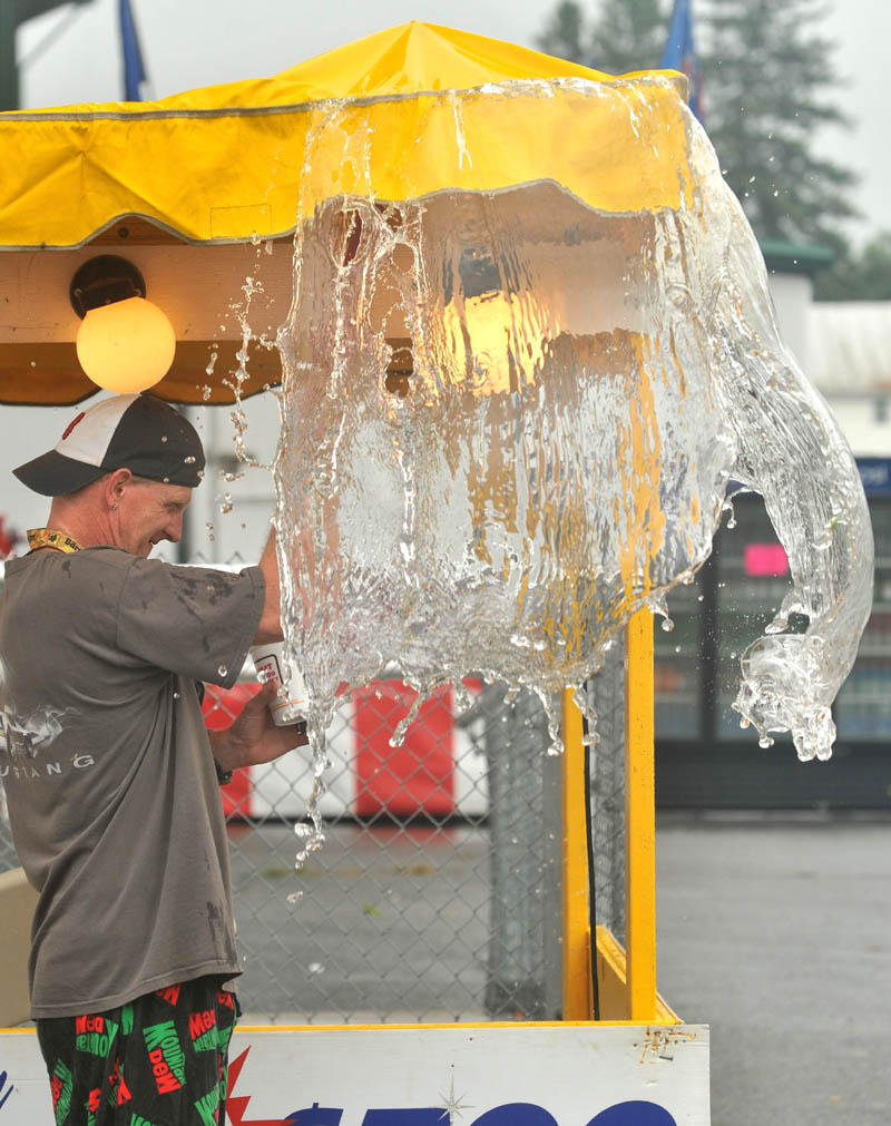 Greg Smith clears water from the ticket tents at the Skowhegan State Fair Friday morning.