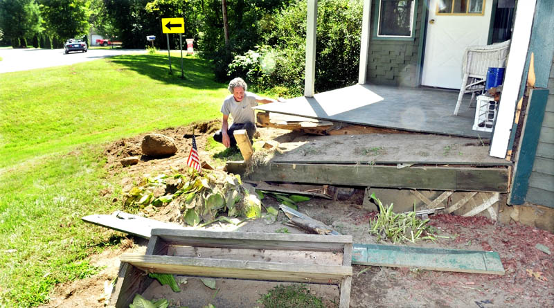 A vehicle drives around a sharp curve on the Hill Road in Canaan as homeowner Robert Spencer examines the damage to his front porch after a truck veered off the road early Monday. Spencer said he woke to squealing tires and the house shook after a truck slammed into his home, injuring two men in the vehicle.