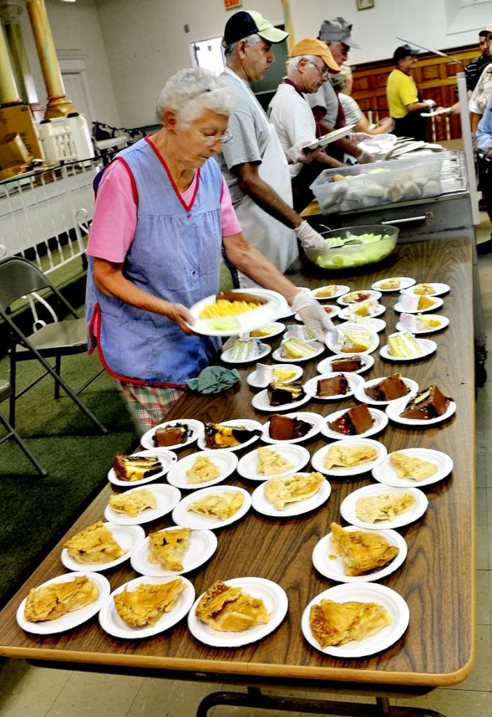 Patricia Stewart and other volunteers serve lunch at the Sacred Heart Soup Kitchen in Waterville on Monday.