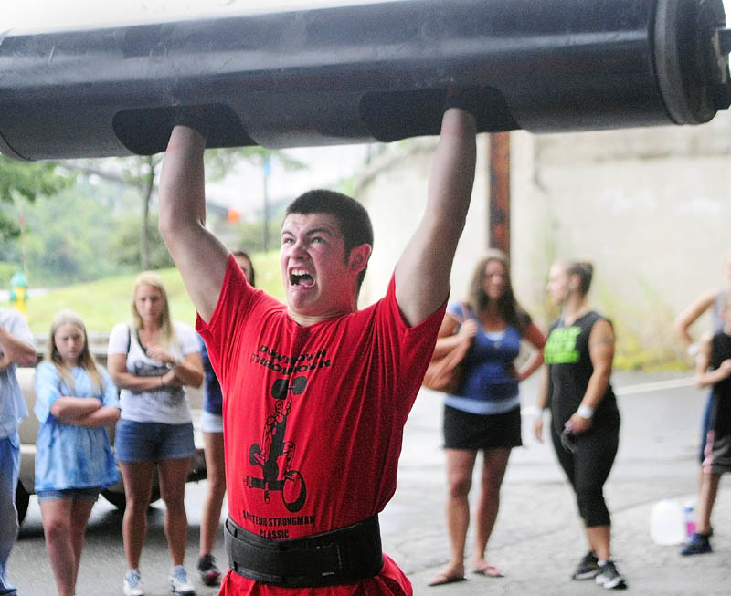STRENGTH: Cody Drummond, of Augusta, strains to lift the bar overhead in the log clean and press event during the Downtown Throwdown strongman contest on Front Street Saturday morning in downtown Augusta.